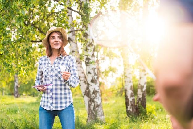 Hermosa mujer jugando bádminton en el parque