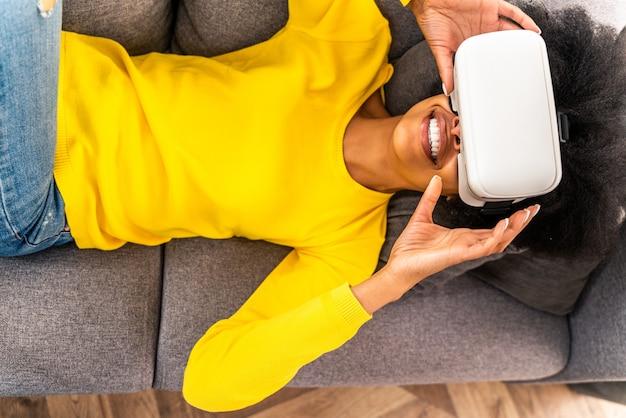 Hermosa mujer jugando en casa con auriculares vr - mujer negra acostada en el sofá mientras interactúa con tecnología de realidad aumentada