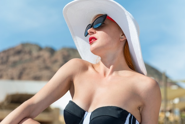 Hermosa mujer junto a la piscina