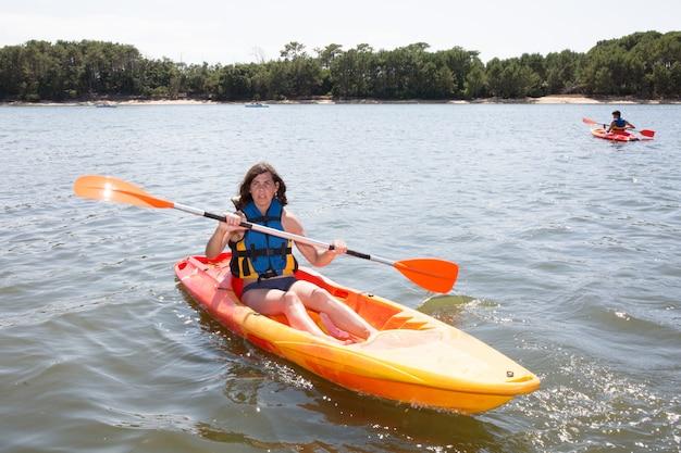 Hermosa mujer kayak en el río durante las vacaciones