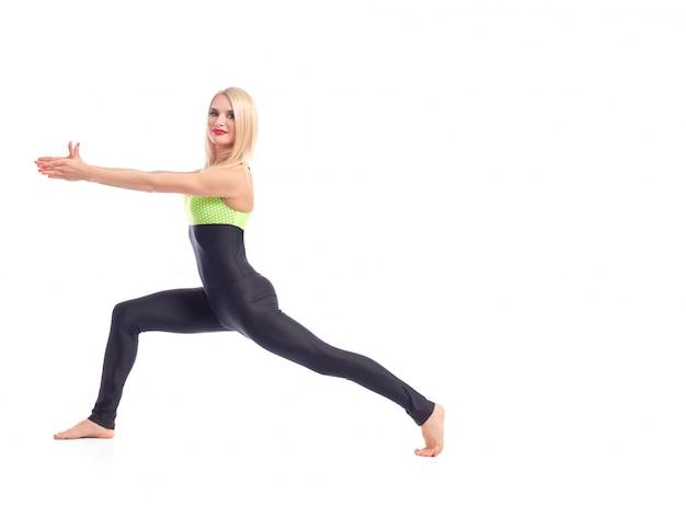 Hermosa mujer de labios rojos en ropa deportiva haciendo asana de yoga guerrera