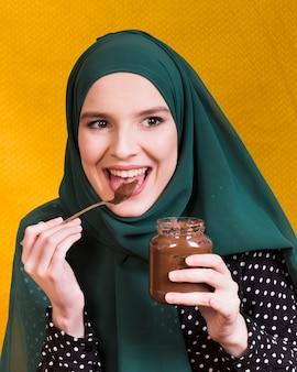Hermosa mujer lamiendo chocolate con tarro y cuchara