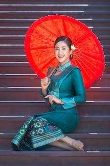 Una hermosa mujer de laos vestida con el traje tradicional de laos. estaba sentado sosteniendo un paraguas rojo en la escalera de la casa de madera