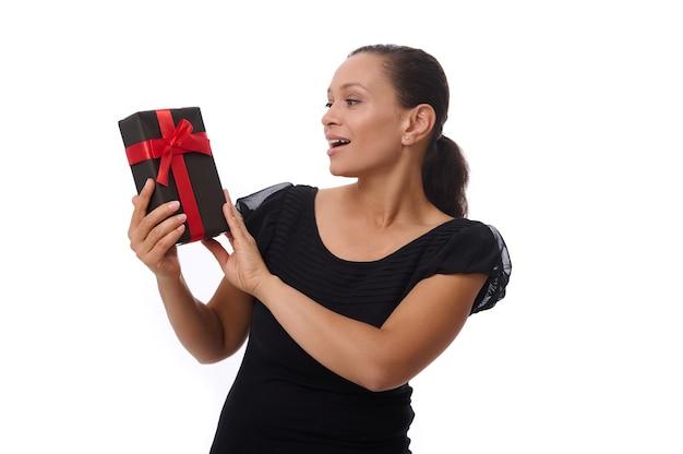 Hermosa mujer latinoamericana feliz vestida con traje negro posa sobre un fondo blanco, sonríe sonrisa con dientes mirando una caja de regalo negra en sus manos. concepto de viernes negro con espacio para texto