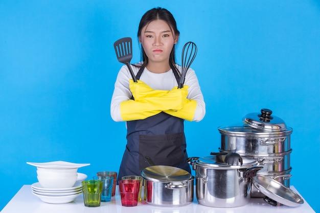 Una hermosa mujer lavando platos frente a él en un azul.