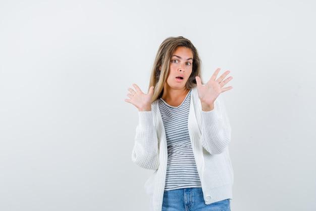Hermosa mujer levantando las manos en gesto de rendición en chaqueta y mirando sorprendido. vista frontal.