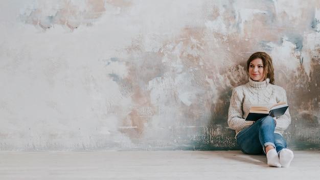 Hermosa mujer leyendo cerca de la pared