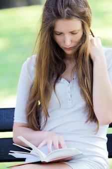 Hermosa mujer leyendo el libro en el parque