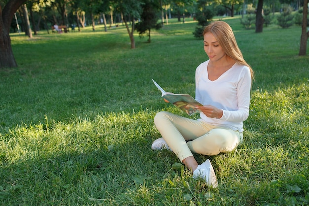 Hermosa mujer leyendo un libro, sentada en el césped, espacio de copia