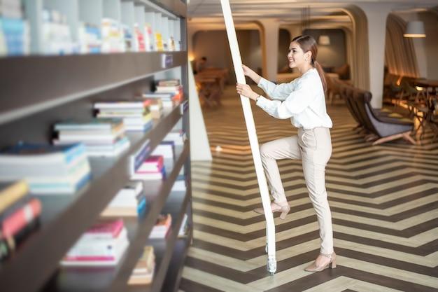 Hermosa mujer está leyendo libros en la biblioteca