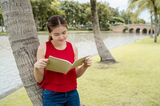 Hermosa mujer leyendo un libro en el parque, ella viste una camisa roja