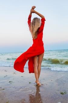 Hermosa mujer libre en vestido rojo en el viento en la playa caminando en verano