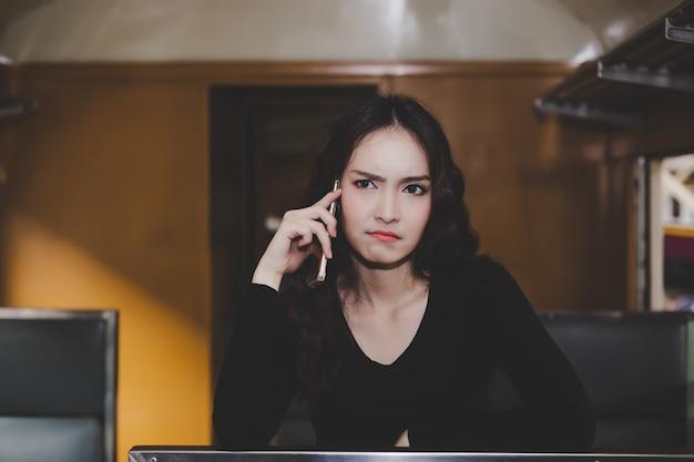 Hermosa mujer está llamando a su novio o amigo que vienen tan tarde.