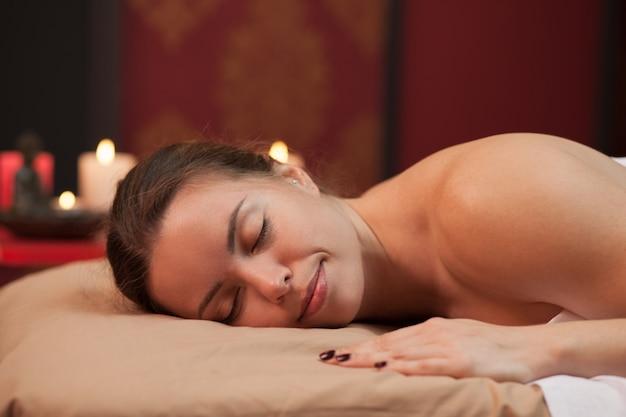 Hermosa mujer madura acostada con los ojos cerrados en el centro de spa, esperando su sesión de masaje. hermosa mujer feliz relajante en clínica de belleza. mujer disfrutando de descanso en el spa resort de lujo.