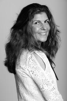 Hermosa mujer madura aislada contra la pared blanca en blanco y negro