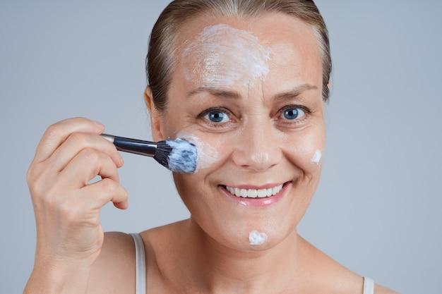 Hermosa mujer madura aplica una mascarilla cosmética a su rostro con un pincel. cuidado de la piel facial en la vejez.