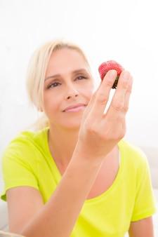 Una hermosa mujer madura comiendo fresas en casa.