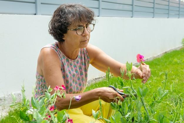 Hermosa mujer madura en un jardín con flores.