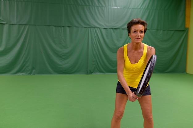 Hermosa mujer madura jugando al tenis en la cancha cubierta