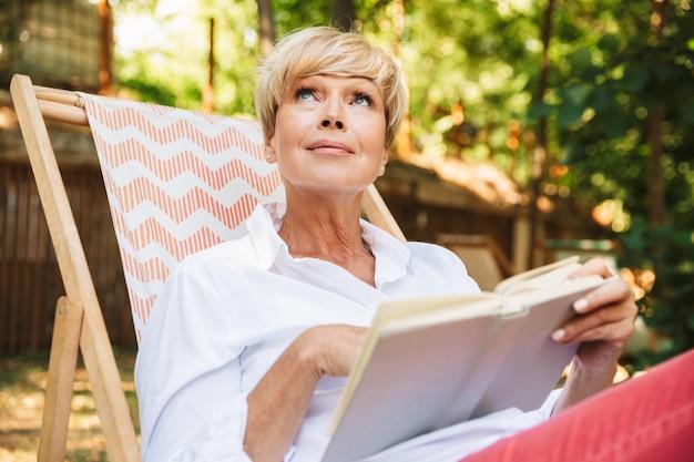 Hermosa mujer madura leyendo un libro mientras descansa