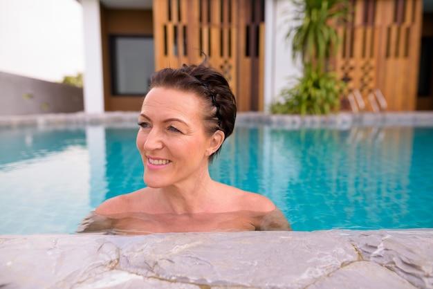 Hermosa mujer madura turista escandinavo en piscina