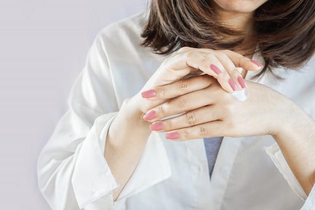 Hermosa mujer mano aplicando crema en sus dedos y uñas