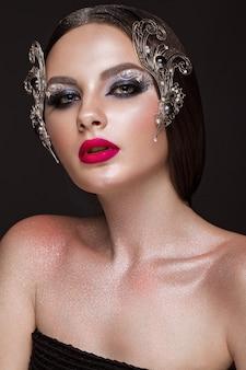 Hermosa mujer con maquillaje artístico creativo y accesorios plateados