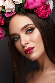 Hermosa mujer con maquillaje brillante y flores en la cabeza