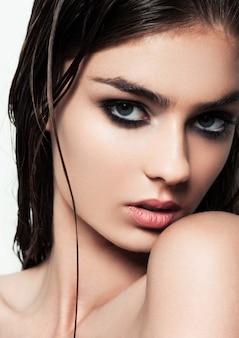 Hermosa mujer con maquillaje y cabello mojado con ojos ahumados y labios rojos