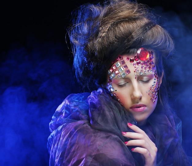 Hermosa mujer con maquillaje creativo brillante