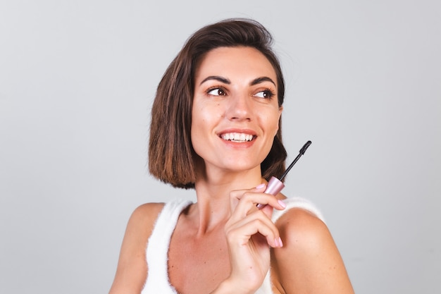 Hermosa mujer con maquillaje mantenga pincel de rímel negro sobre pared gris, concepto de belleza
