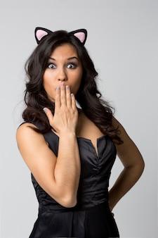Hermosa mujer de maquillaje mostrando silencio firmar los dedos cerca de los labios en luz aislada