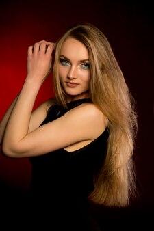 Hermosa mujer con maquillaje natural y exuberante cabello rubio en el estudio