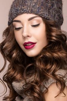 Hermosa mujer con maquillaje suave, rizos en sombrero de punto marrón
