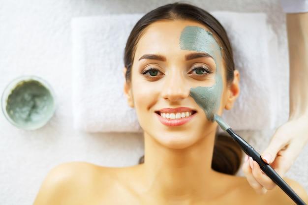 Hermosa mujer con máscara cosmética en la cara. chica recibe tratamiento en el salón de spa. mascarilla casera para rostro. tratamientos de spa.