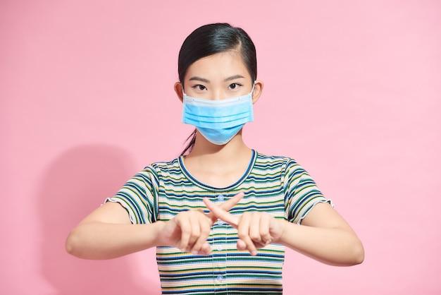 Hermosa mujer en máscara quirúrgica facial muestra parada con el dedo, gesto para detener el virus corona