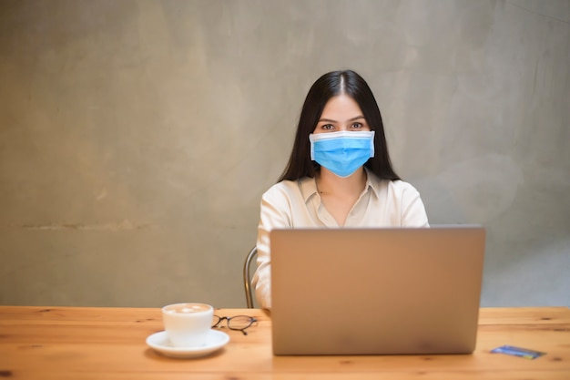Hermosa mujer con máscara está trabajando en la computadora portátil en la cafetería