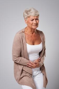 Hermosa mujer mayor tiene dolor de estómago