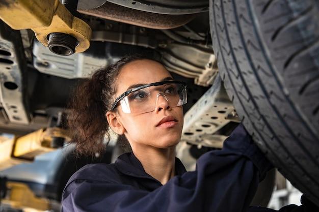 Hermosa mujer mecánica en uniforme está trabajando en servicio automático con vehículo levantado e informes.