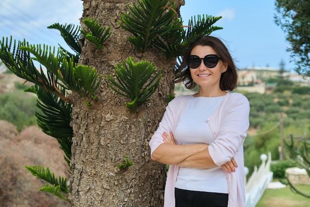 Hermosa mujer de mediana edad con los brazos cruzados, mujer con gafas de sol cerca de árbol tropical