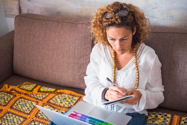 Hermosa mujer de mediana edad que trabaja en casa con una computadora portátil mientras está sentado en el sofá. tomando notas y mirando el escritorio de la computadora. oficina de internet estilo de vida alternativo