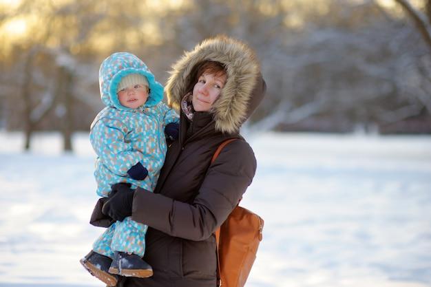 Hermosa mujer de mediana edad y su adorable nieto en el parque de invierno
