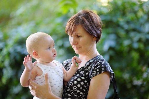 Hermosa mujer de mediana edad y su adorable nieto en el parque de verano