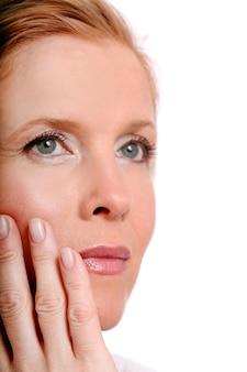 Hermosa mujer de mediana edad toca su rostro