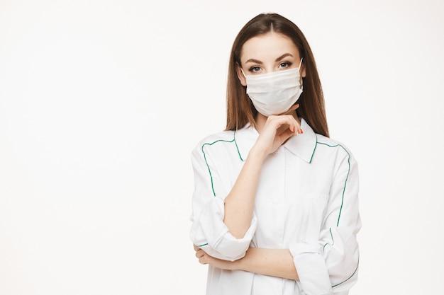 Hermosa mujer médico o enfermera con máscara protectora y bata médica posando. mujer joven en uniforme médico. concepto de salud