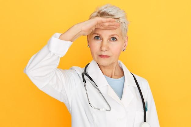 Hermosa mujer médico senior con peinado corto teñido y ojos azules manteniendo la mano en la frente buscando algo lejano en la distancia.