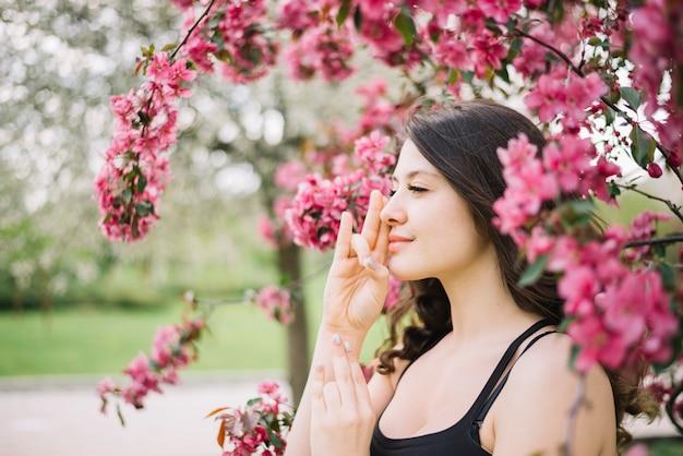 Hermosa mujer meditación con gesto mudra cerca del árbol en el jardín