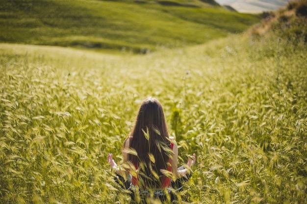 Hermosa mujer meditando en el campo verde