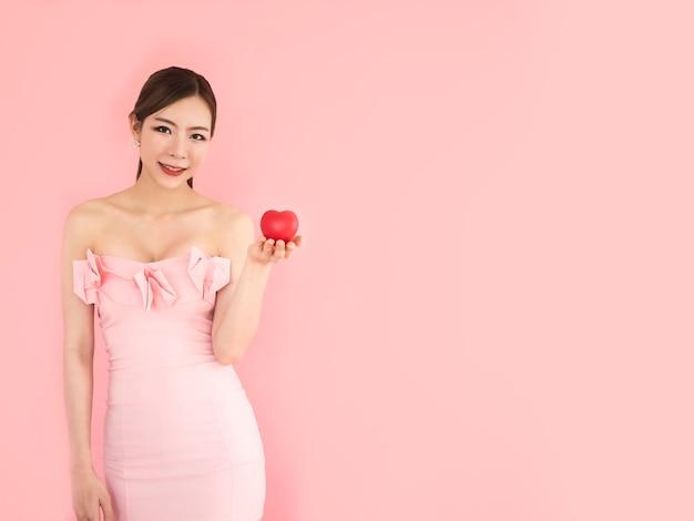 Hermosa mujer con mini corazón en mano, chica de moda en fondo rosa