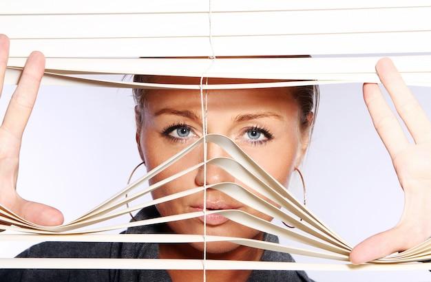 Hermosa mujer mira a través de persianas